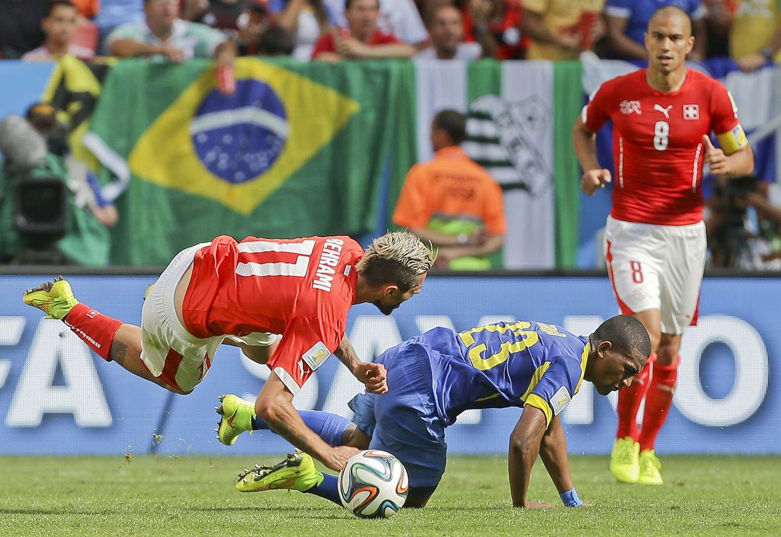 Switzerland's Valon Behrami, left, is fouled by Ecuador's Carlos Gruezo during the group E World Cup soccer match between Switzerland and Ecuador at the Estadio Nacional in Brasilia, Brazil, Sunday, June 15, 2014.  The referee played the advantage rule and the Swiss carried on to score the winning goal. (AP Photo/Martin Mejia)