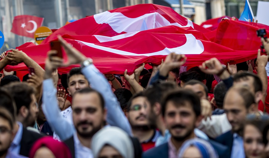 epa06825439 Supporters of Turkish President Recep Tayyip Erdogan carry a large Turkish flag during an election campaign rally of Justice and Development Party (AK Party) in Istanbul, Turkey, 20 June 2018. Turkish President Erdogan announced on 18 April 2018 that Turkey will hold snap elections on 24 June 2018. The presidential and parliamentary elections were scheduled to be held in November 2019, but government has decided to change the date following the recommendation of the Nationalist Movement Party (MHP) leader Devlet Bahceli.  EPA/SRDJAN SUKI