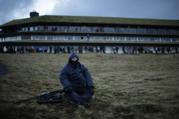 A visitor waits for the start of a total solar eclipse on a hill beside a hotel overlooking Torshavn, the capital city of the Faeroe Islands, Friday, March 20, 2015. For months, even years, accommodation on the remote Faeroe Islands has been booked out by fans who don't want to miss an almost three-minute-long astronomical sensation. Now they just have to hope the clouds will blow away so they can fully experience Friday's brief total solar eclipse.  (AP Photo/Matt Dunham)