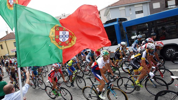 epa04338077 Tha pack of cyclists passes by Portuguese flags during the second stage of the 76th CyclingTour of Portugal between Gondomar and Braga, in Braga, Portugal, 01 August 2014. The Tour of Portugal runs until 10 August.  EPA/NUNO VEIGA