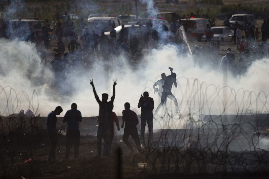 Palestinians protesters run from tear gas fired by Israeli troops in Israel Gaza border, Friday, June 8, 2018. (AP Photo/Ariel Schalit)