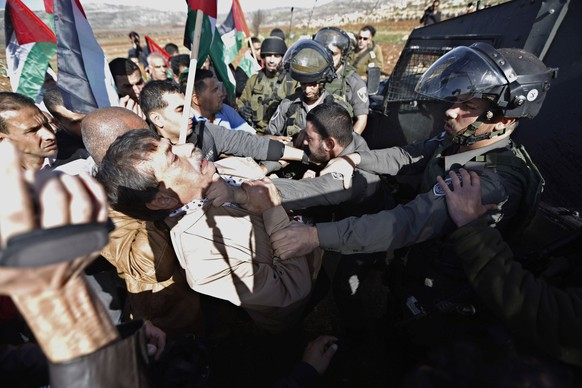 Palestinian minister Ziad Abu Ein (L) scuffles with an Israeli border policeman near the West Bank city of Ramallah December 10, 2014. Abu Ein died shortly after being hit by Israeli soldiers during a protest on Wednesday in the occupied West Bank, a Reuters photographer who witnessed the incident and a Palestinian medic said. Ziad Abu Ein, a minister without portfolio who was in his early 50s, was rushed by ambulance from the scene, in the village of Turmusiya, but died en route to the nearby Palestinian city of Ramallah. The Israeli army was looking into the incident, a spokeswoman said, She did not immediately provide further information.  REUTERS/Mohamad Torokman (WEST BANK - Tags: POLITICS CIVIL UNREST MILITARY PROFILE TPX IMAGES OF THE DAY)
