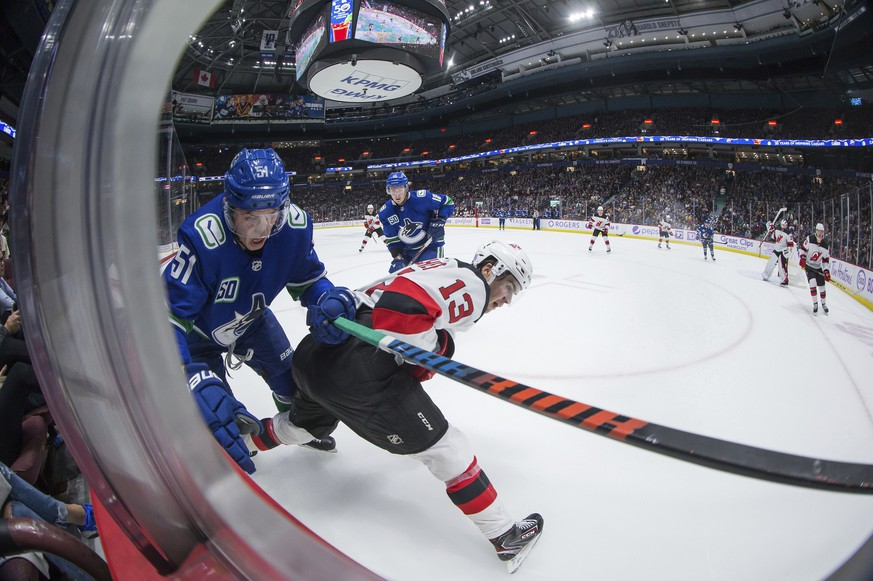 Vancouver Canucks' Troy Stecher (51) and New Jersey Devils' Nico Hischier (13), of Switzerland, collide during the second period of an NHL hockey game in Vancouver, British Columbia, Sunday, Nov. 10, 2019. (Darryl Dyck/The Canadian Press via AP)