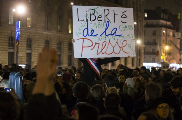 epa04550042 A participant holds a placard with the words; 'Freedom of the Press', as thousands gather for a candle light vigil on Place de la Republique in central Paris hours after the attack by  two gunmen on the 'Charly Hebdo' headquarters in Paris, France, 07 January 2015. According to news reports, 12 people have been killed in a shooting attack at satirical French magazine Charlie Hebdo in Paris.  EPA/IAN LANGSDON