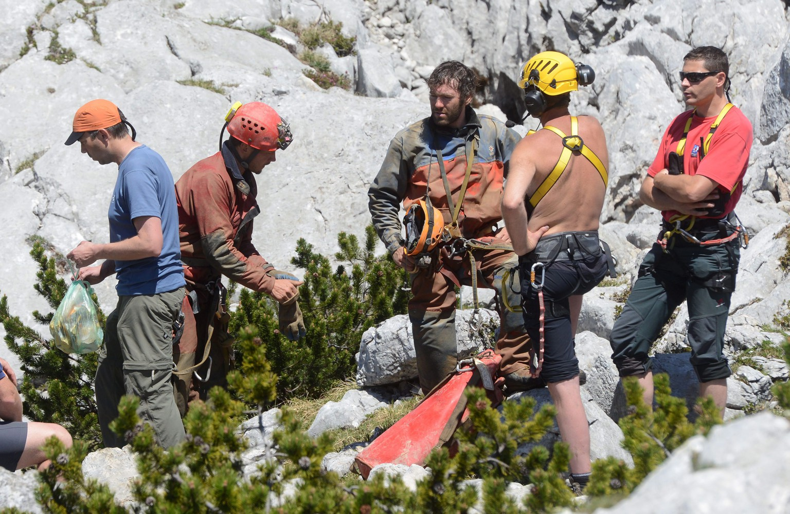epa04249643 Two German cave rescuers (2-L and 3-L) talk to each other after a rescue mission inside Riesending-Schachthoehle cave at Untersberg mountain near Marktschellenberg, Germany, 11 June 2014. Teams from Italy have arrived to help prepare the shaft for the rescue, after an injured German spelunker had been severly injured and trapped nearly a kilometer below ground since a rockslide two days earlier. The man was with two companions when the rockslide struck early in the Riesending, which translates to Big Thing and is Germany's deepest cave. His companions escaped without significant injury.  EPA/TOBIAS HASE