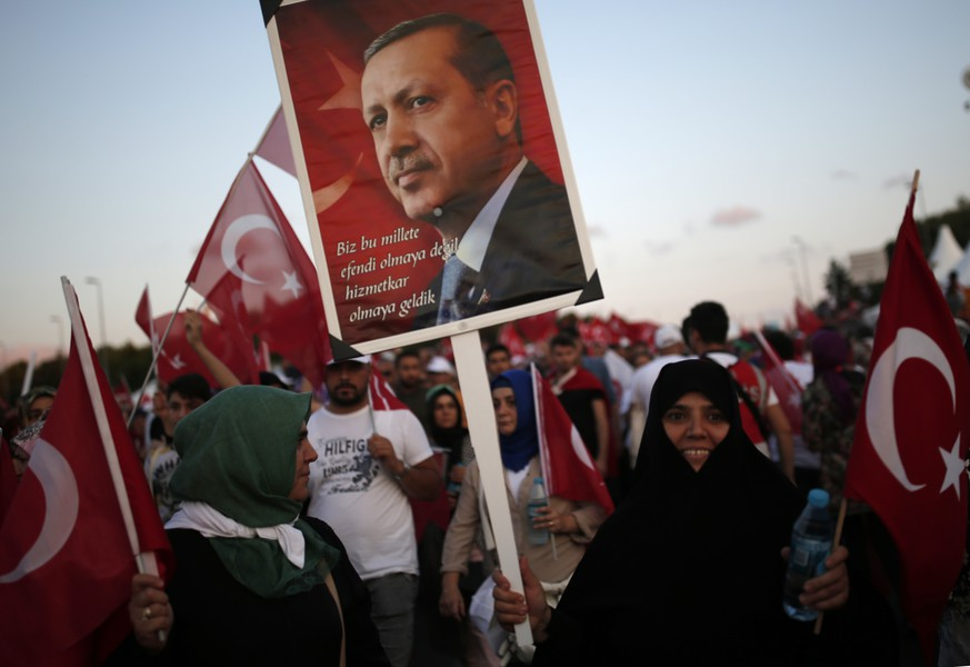 A woman holds placard depicting Turkish president Erdogan during