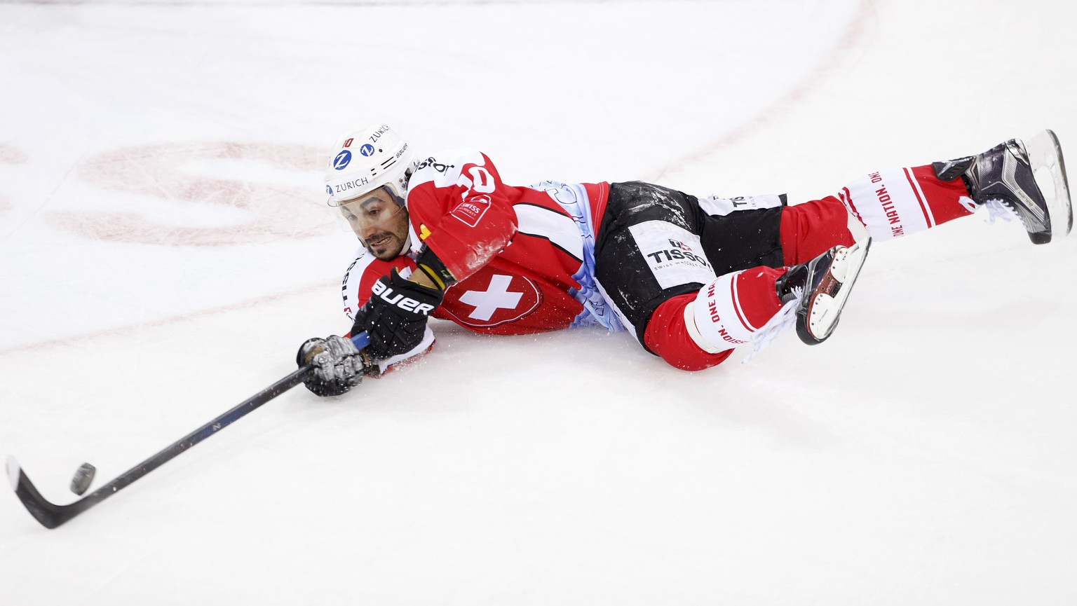 Switzerland's Andres Ambuehl tries to catch the puck, during friendly ice hockey game between Switzerland and Latvia, at the ice stadium Les Vernets, in Geneva, Switzerland, Friday, April 29, 2016. (KEYSTONE/Salvatore Di Nolfi)