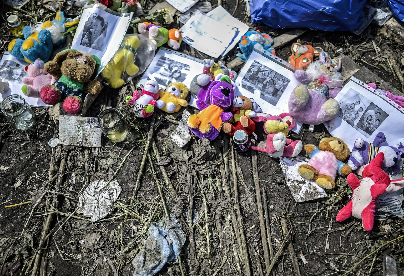 Soft toys and pictures are seen amongst the wreckage of the Malaysia Airlines flight MH17 near the village of Grabove, in the region of Donetsk on July 20, 2014. The missile system used to shoot down a Malaysian airliner was handed to pro-Russian separatists in Ukraine by Moscow, the top US diplomat said Sunday. Outraged world leaders have demanded Russia's immediate cooperation in a prompt and independent probe into the shooting down on July 17 of flight MH17 with 298 people on board. AFP PHOTO/ BULENT KILIC