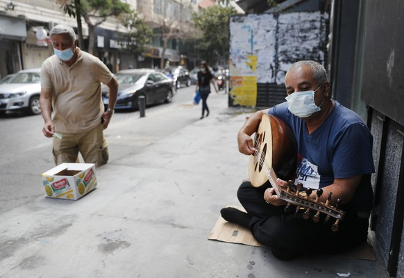 A street musician man performs with a mask on his face to help stop the spread of the coronavirus, as other man on the left puts money on a box, in Beirut, Lebanon, Wednesday, July 29, 2020.  Lebanon is hurtling toward a tipping point at an alarming speed, driven by financial ruin, collapsing institutions, hyperinflation and rapidly rising poverty _ with a pandemic on top of that. The collapse threatens to break a nation seen as a model of diversity and resilience in the Arab world. (AP Photo/Hussein Malla)