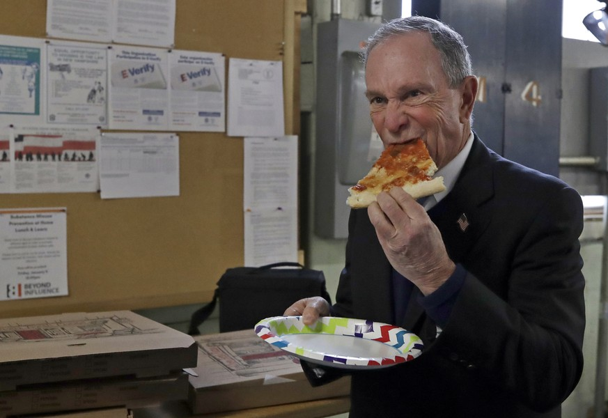 Potential Democratic presidential candidate Michael Bloomberg eats a slice of pizza after a tour of the WH Bagshaw Company, a pin and precision component manufacturer, Tuesday Jan. 29, 2019, in Nashua, N.H. (AP Photo/Elise Amendola)