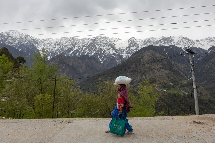 Snow-covered peaks of the Dhauladhar range of the Himalaya are seen in the background as a woman carries rations from a shop during a relaxation in the curfew put in place to check the spread of the coronavirus in Dharmsala, India, Tuesday, April 7, 2020. The new coronavirus causes mild or moderate symptoms for most people, but for some, especially older adults and people with existing health problems, it can cause more severe illness or death. (AP Photo/Ashwini Bhatia)