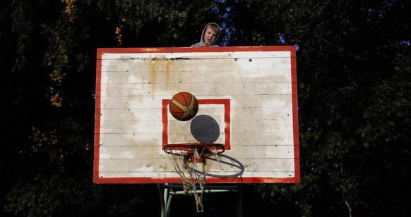 A child looks on the ball as he stands on a backboard in Alytus, Lithuania,on Friday, Sept. 2, 2011. Basketball is the most popular and the most successful team sport in Lithuania.The European Basketball Championship 2011 started in Lithuania on Wednesday, Aug. 31, with the Group stages and will be finished on Sunday, Sept, 18, with the final. (AP Photo/Petros Giannakouris)