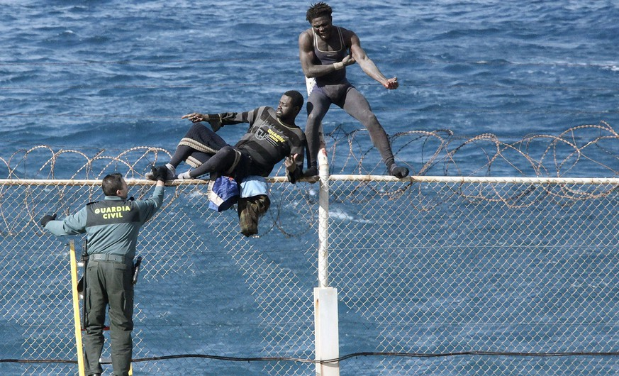 epa04986346 YEARENDER 2015 FEBRUARY Two immigrants try to jump over the Ceuta border fence, the Spanish enclave on the north coast of Africa, 03 February 2015.  EPA/REDUAN *** Local Caption *** 51780302
