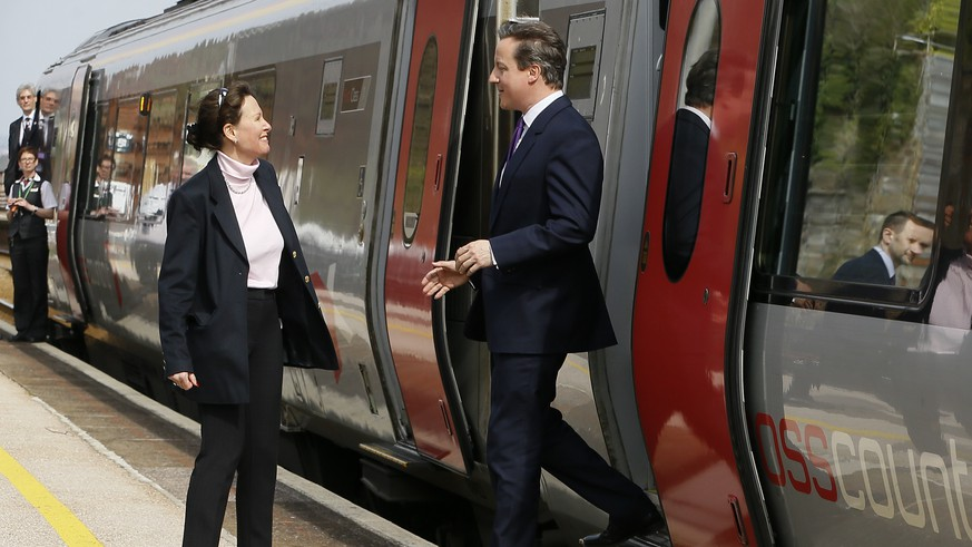 Britain's Prime Minister David Cameron is met by Conservative candidate Anne Marie Morris as he steps off a train in Dawlish, in Devon, England, Friday, April 10, 2015. Britain goes to the polls in a General Election on May 7. (AP Photo/Kirsty Wigglesworth, pool)