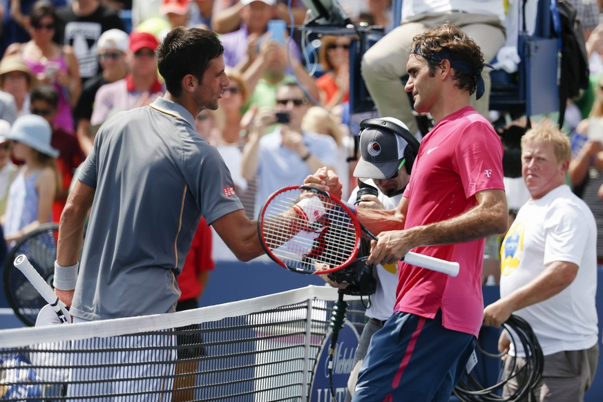 Roger Federer, right, of Switzerland, clasps hands with Novak Djokovic, of Serbia, after the men's final at the Western & Southern Open tennis tournament, Sunday, Aug. 23, 2015, in Mason, Ohio. Federer defeated Djokovic 7-6 (1), 6-3. (AP Photo/John Minchillo)