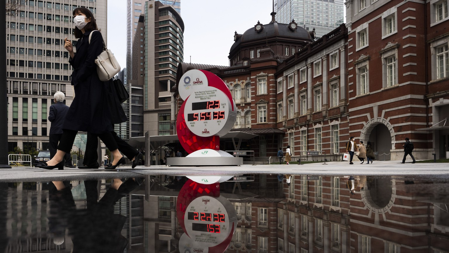 A countdown clock for the Tokyo 2020 Olympics is reflected in a puddle of water outside Tokyo Station in Tokyo, Monday, March 23, 2020. The IOC will take up to four weeks to consider postponing the Tokyo Olympics amid mounting criticism of its handling of the coronavirus crisis that now includes Canada saying it won't send a team to the games this year and the leader of track and field, the biggest sport at the games, also calling for a delay. (AP Photo/Jae C. Hong)