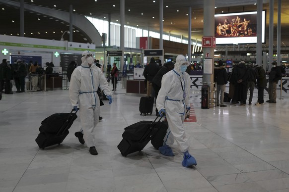 Passengers from Taiwan wearing protective gear arrive to board their plane at Paris Charles de Gaulle Airport in Roissy , north of Paris, Monday, Feb. 1, 2021. France says it's closing its borders to people arriving from outside the European Union starting Sunday to try to stop the growing spread of new variants of the virus and avoid a third lockdown. (AP Photo/Francois Mori)
