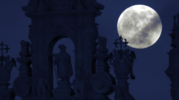 epa07304243 The full moon rises over the St James statue in the Cathedral of Santiago de Compostela, Galicia, northern Spain, 20 January 2019, hours ahead of a lunar eclipse, which some are referring to as a 'super blood wolf moon'. The entire eclipse will be visible from North and South America, as well as parts of western Europe and north Africa.  EPA/Lavandeira jr