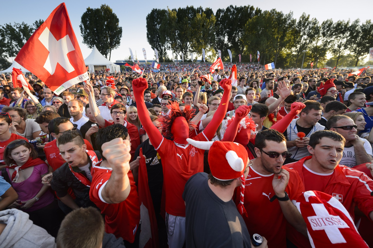 Swiss soccer fans cheer during the live broadcast of the Brazil Soccer FIFA World Cup match between Switzerland and France at the public viewing zone in Lausanne, Switzerland, Friday, June 20, 2014. (KEYSTONE/Laurent Gillieron)