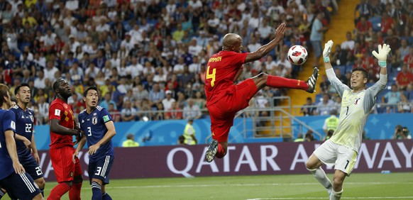 Players watching Belgium's Vincent Kompany jumping with the ball in front of Japan goalkeeper Eiji Kawashima during the round of 16 match between Belgium and Japan at the 2018 soccer World Cup in the Rostov Arena, in Rostov-on-Don, Russia, Monday, July 2, 2018. (AP Photo/Petr David Josek)