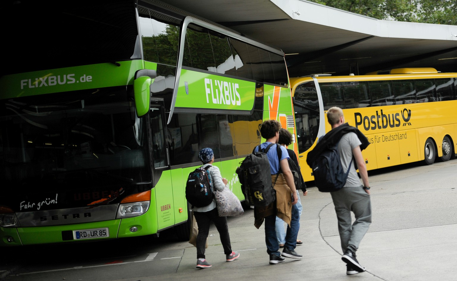 Passengers walk near Flixbus and Postbus busses at the main bus station (ZOB) in Berlin, Germany August 3, 2016. REUTERS/Stefanie Loos