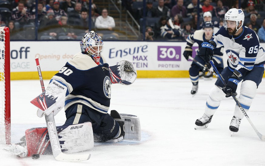 Columbus Blue Jackets' Elvis Merzlikins, left, of Latvia, makes a save against Winnipeg Jets' Mathieu Perreault during the third period of an NHL hockey game Wednesday, Jan. 22, 2020, in Columbus, Ohio. The Blue Jackets defeated the Jets 4-3. (AP Photo/Jay LaPrete)