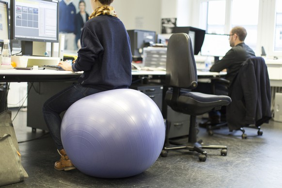 Two people sit at desks using an office chair and a sitting ball, pictured in Zurich, Switzerland, on February 7, 2014. (KEYSTONE/Gaetan Bally)