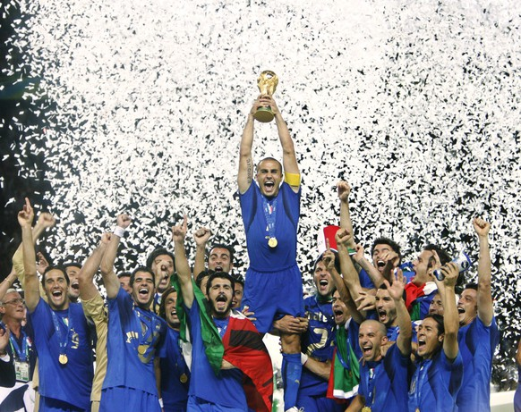 FILE - In this Sunday, July 9, 2006 file photo Fabio Cannavaro lifts the soccer World Cup trophy after Italy defeated France in the final in the Olympic Stadium in Berlin, Germany. The World Cup was in full swing when the U.S. Federal Reserve last raised interest rates before its decision Wednesday, Dec. 16, 2015, to lift its main interest rate from record lows of near zero percent. (AP Photo/Luca Bruno, File)
