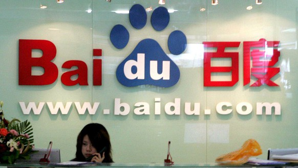 FILE - In this July 28, 2005 file photo, a receptionist works behind the logo for Baidu.com, a Chinese language search engine, at the company's office in Beijing. Baidu Inc., which operates China's most popular Internet search engine, said Wednesday Feb. 10, 2010, its quarterly earnings jumped 48 percent, beating analysts' expectations on strong revenue growth. (AP Photo/Ng Han Guan, File)