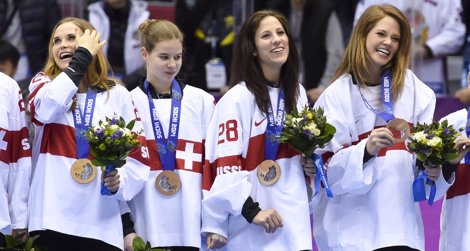 Switzerland's ice hockey women goalkeepers Florence Schelling, right, and Sophie Anthamatten, second from right, celebrate their bronze medal during the women's ice hockey victory ceremony at the XXII Winter Olympics 2014 Sochi, at the Bolshoy Ice Dome, in Sochi, Russia, on Thursday, February 20, 2014. (KEYSTONE/Laurent Gillieron)