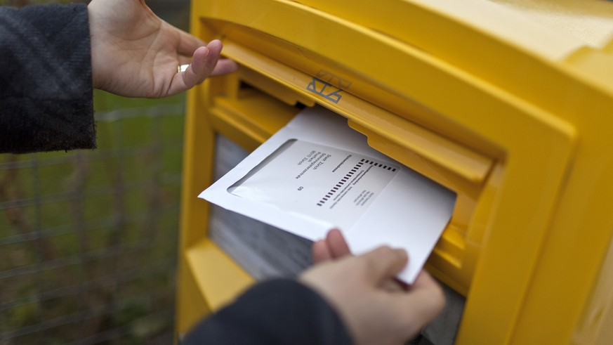 A woman drops an envelope with her vote-by-mail ballot in a letterbox on the occasion of the second tour of the election for the canton of Zurich's seat in the federal Council of States, pictured on November 23, 2011, in Zurich, Switzerland. (KEYSTONE/Gaetan Bally)  Eine Frau wirft ein Couvert mit ihren Wahlunterlagen in einen Briefkasten, aufgenommen am 23. November 2011 in Zuerich. (KEYSTONE/Gaetan Bally)