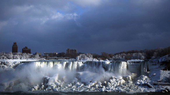 Water flows over the American Falls as ice forms in this view from the Canadian side in Niagara Falls, Ont., Tuesday, Jan. 2, 2018.  Almost every year frigid temperatures transform the falls into an icy winter wonderland when the mist is blown back, freezing on the landscape.  (Aaron Lynett/The Canadian Press via AP)