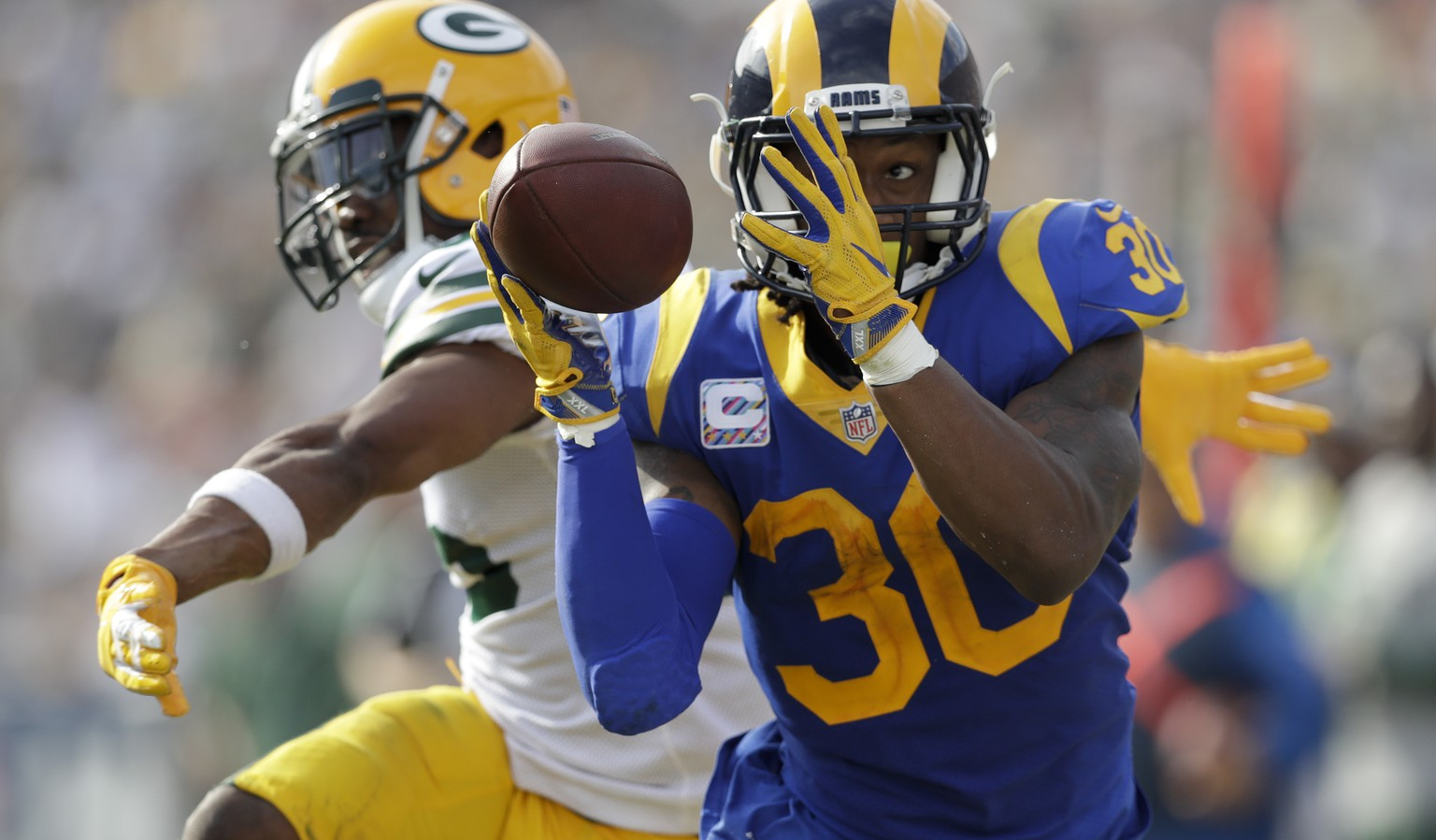Los Angeles Rams running back Todd Gurley makes a catch as Green Bay Packers defensive back Jermaine Whitehead defends during the first half of an NFL football game, Sunday, Oct. 28, 2018, in Los Angeles. (AP Photo/Marcio Jose Sanchez)
