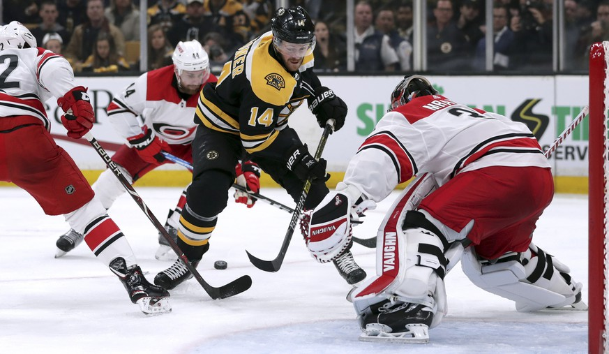 The puck slides behind Boston Bruins' Chris Wagner (14) as he closes in on Carolina Hurricanes goaltender Petr Mrazek, right, of the Czech Republic, during the second period in Game 2 of the NHL hockey Stanley Cup Eastern Conference final series, Sunday, May 12, 2019, in Boston. (AP Photo/Charles Krupa)