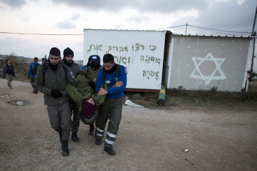 epa05764828 Israeli security forces arrest a settler during the evacuation of the illegal Jewish settlement of Amona, in the West Bank, 01 February 2017. Israeli police have deployed 3,000 policemen around the settlement for a planned eviction ordered by the Israeli Supreme Court.  EPA/ABIR SULTAN