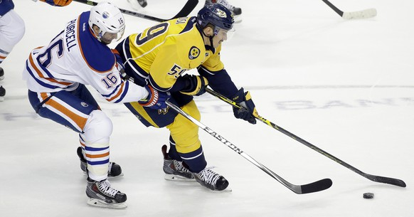 Nashville Predators defenseman Roman Josi (59), of Switzerland, takes the puck past Edmonton Oilers right wing Teddy Purcell (16) in the first period of an NHL hockey game Tuesday, Nov. 11, 2014, in Nashville, Tenn. (AP Photo/Mark Humphrey)