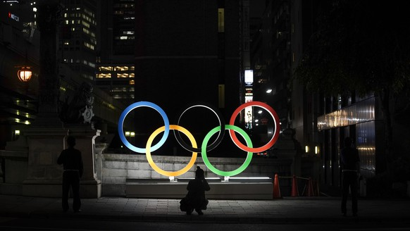 A photographer takes pictures of the Olympic rings Tuesday, July 23, 2019, in Tokyo, as Japan marks a year-to-go until hosting the summer games with Olympic medals being unveiled Wednesday as part of daylong ceremonies around the Japanese capital.  The Summer Olympics will return to Tokyo next year for the first time since 1964. (AP Photo/Jae C. Hong)