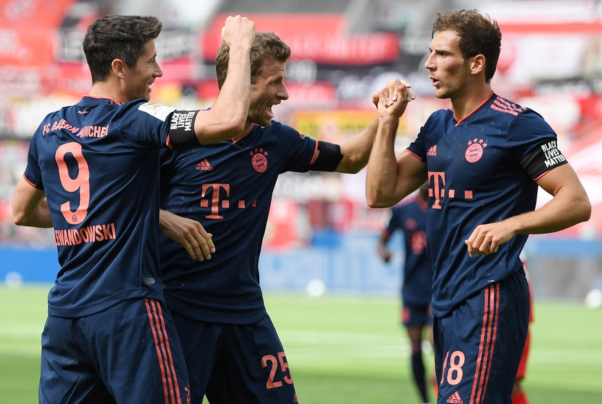 epa08469277 Robert Lewandowski of Muenchen (L) celebrates his team's fourth goal with teammates Thomas Mueller and Leon Goretzka (L-R) during the Bundesliga match between Bayer 04 Leverkusen and FC Bayern Munich at BayArena in Leverkusen, Germany, 06 June 2020.  EPA/MATTHIAS HANGST / POOL DFL regulations prohibit any use of photographs as image sequences and/or quasi-video.