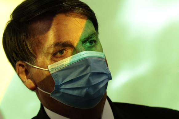 President Jair Bolsonaro wears a mask amid the COVID-19 pandemic at the start of a ceremony where the national flag is projected in Brasilia, Brazil, Wednesday, Aug. 5, 2020. (AP Photo/Eraldo Peres) Jair Bolsonaro