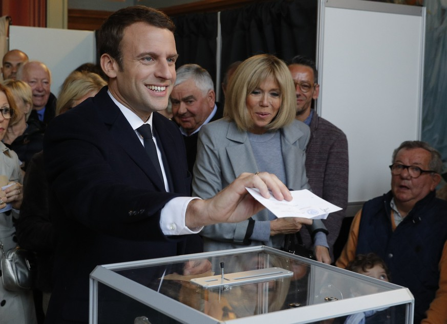 epa05922886 Brigitte Trogneux (R), wife of Emmanuel Macron (L), head of the political movement En Marche! (Onwards!) and candidate for the 2017 French presidential election, watches her husband casting his ballot in the first round of 2017 French presidential election at a polling station in Le Touquet, northern France, 23 April 2017. France will hold the second round of the presidential elections on 07 May 2017.  EPA/PHILIPPE WOJAZER / POOL MAXPPP OUT