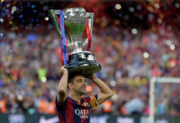 FC Barcelona's Xavi Hernandez holds up the trophy after winning the Spanish League title, at the end of their Spanish La Liga last round soccer match against Deportivo Coruna at the Camp Nou stadium in Barcelona, Spain, Saturday, May 23, 2015. (AP Photo/Manu Fernandez)
