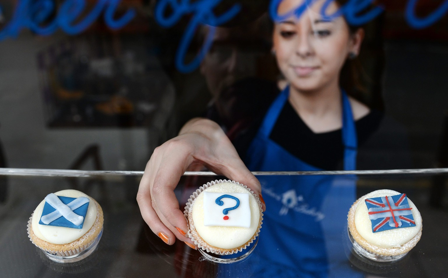 epaselect epa04402457 A bakery employee places a 'question mark' cupcake between a Scottish Saltire cake (L) and a Union cupcake (R) at a bakery in Edinburgh, Scotland, 16 September 2014. Polls are showing that the Yes and No camps are neck and neck in the Scottish Independence referendum. Scots will vote wether Scotland should become an independent country on 18 September.  EPA/ANDY RAIN