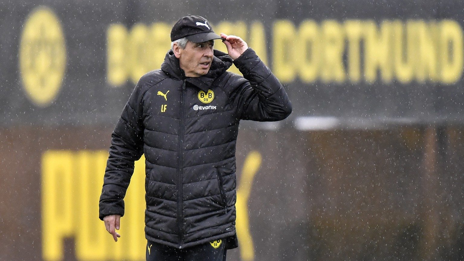 Dortmund's head coach Lucien Favre arrives in the rain during a training session in Dortmund, Germany, Monday, Nov. 4, 2019. Borussia Dortmund plays Inter Milan in a Champions League Group F soccer match in Dortmund on Tuesday. (AP Photo/Martin Meissner)