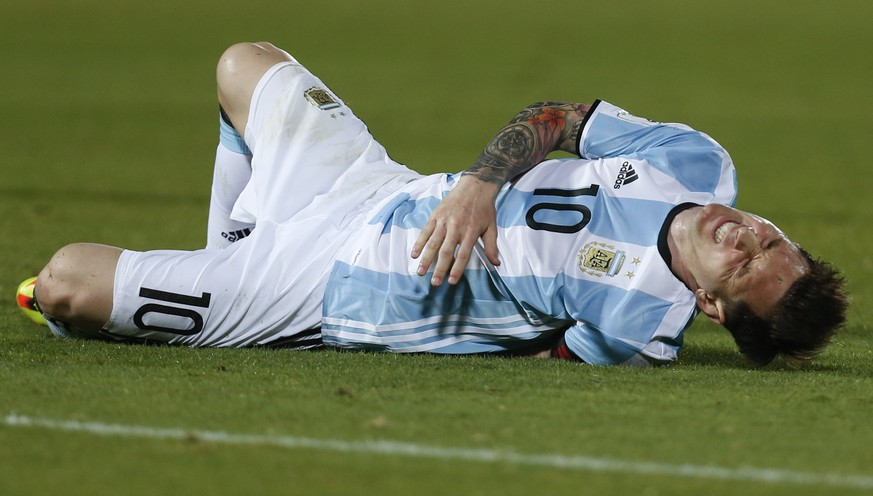 Argentina's Lionel Messi grimaces after being fouled during a 2018 Russia World Cup qualifying soccer match against Chile at the National Stadium in Santiago, Chile, Thursday, March 24, 2016. (AP Photo/ Luis Hidalgo)