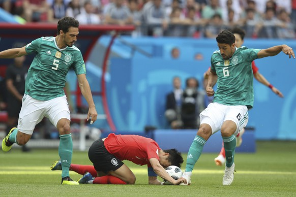 South Korea's Son Heung-min, center, is tackled by Germany's Mats Hummels, left, and Germany's Sami Khedira during the group F match between South Korea and Germany, at the 2018 soccer World Cup in the Kazan Arena in Kazan, Russia, Wednesday, June 27, 2018. (AP Photo/Thanassis Stavrakis)