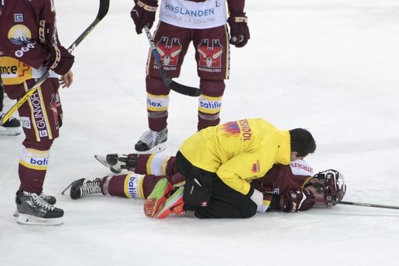 Noah Rod, Mitte, von Servette, liegt nach einem zusammenstoss benommen auf dem Eis beim Eishockey Meisterschaftsspiel zwischen dem EV Zug und Geneve Servette HC vom Montag, 2. Januar 2017, in Zug. (KEYSTONE/Urs Flueeler)
