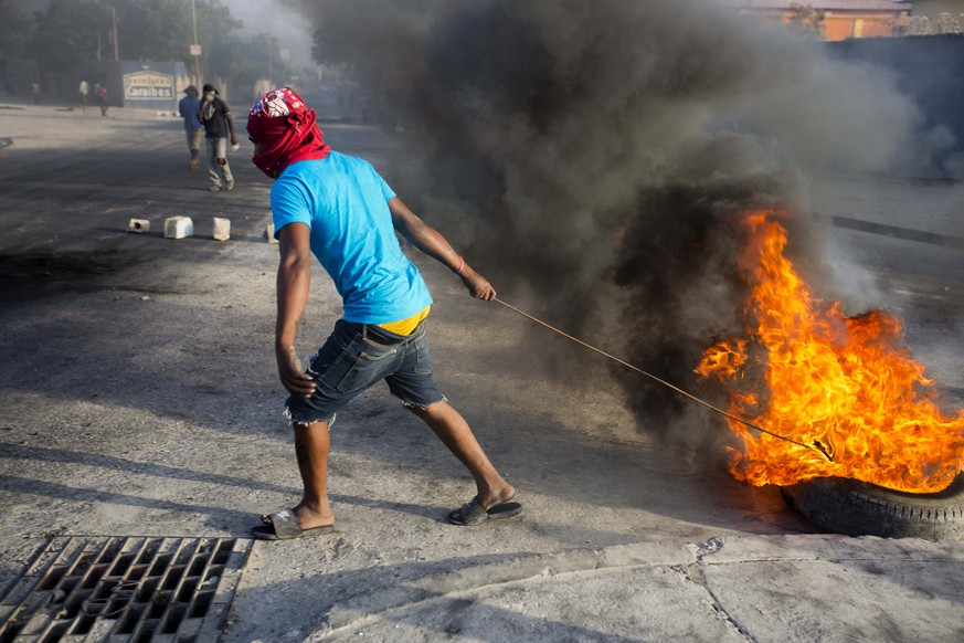 A protester pulls a burning tire in the middle of the street during a protest over the cost of fuel in Port-au-Prince, Haiti, Saturday, July 7, 2018. Major protests erupted Friday in Haiti as the government announced a sharp increase in gasoline prices. (AP Photo/Dieu Nalio Chery)