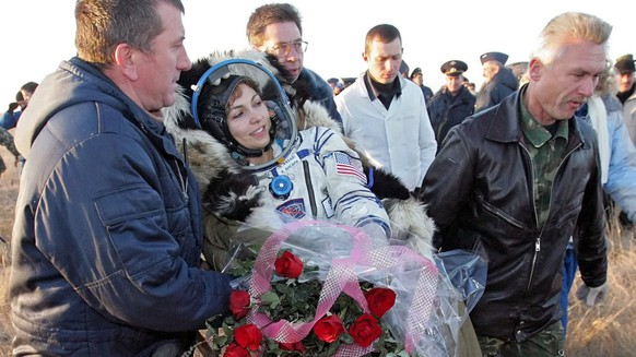 Russian search and recover specialists carry U.S. entrepreneur and the world's first female space tourist Anousheh Ansari shortly after landing of Russian Souyz space capsule not far from Kazakh town of Arkalyk in northern Kazakhstan (some 500 km from Kazakh capital of Astana) early Friday 29 September 2006 with US NASA astronaut Jeffrey Williams and Russian cosmonaut Pavel Vinogradov.  EPA/SERGEI ILNITSKY