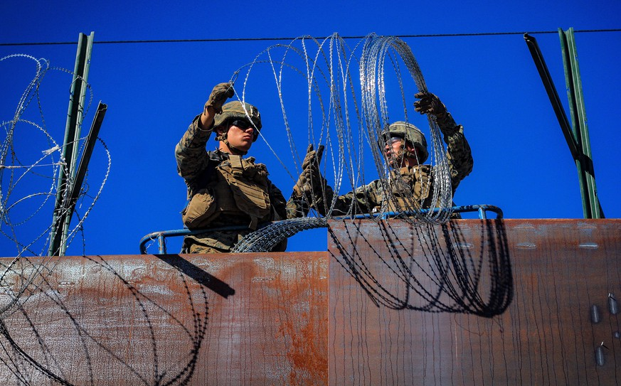epa07161704 US military soldiers install barbed wire on the border with Mexico as seen from Colonia Libertad in Tijuana, Mexico, 12 November 2018. Around 4,000 migrants departed in the morning from Irapuato, in the central state of Guanajuato, to Guadalajara, about 252 kilometers away, on their way to the US border.  EPA/JOEBETH TERRIQUEZ