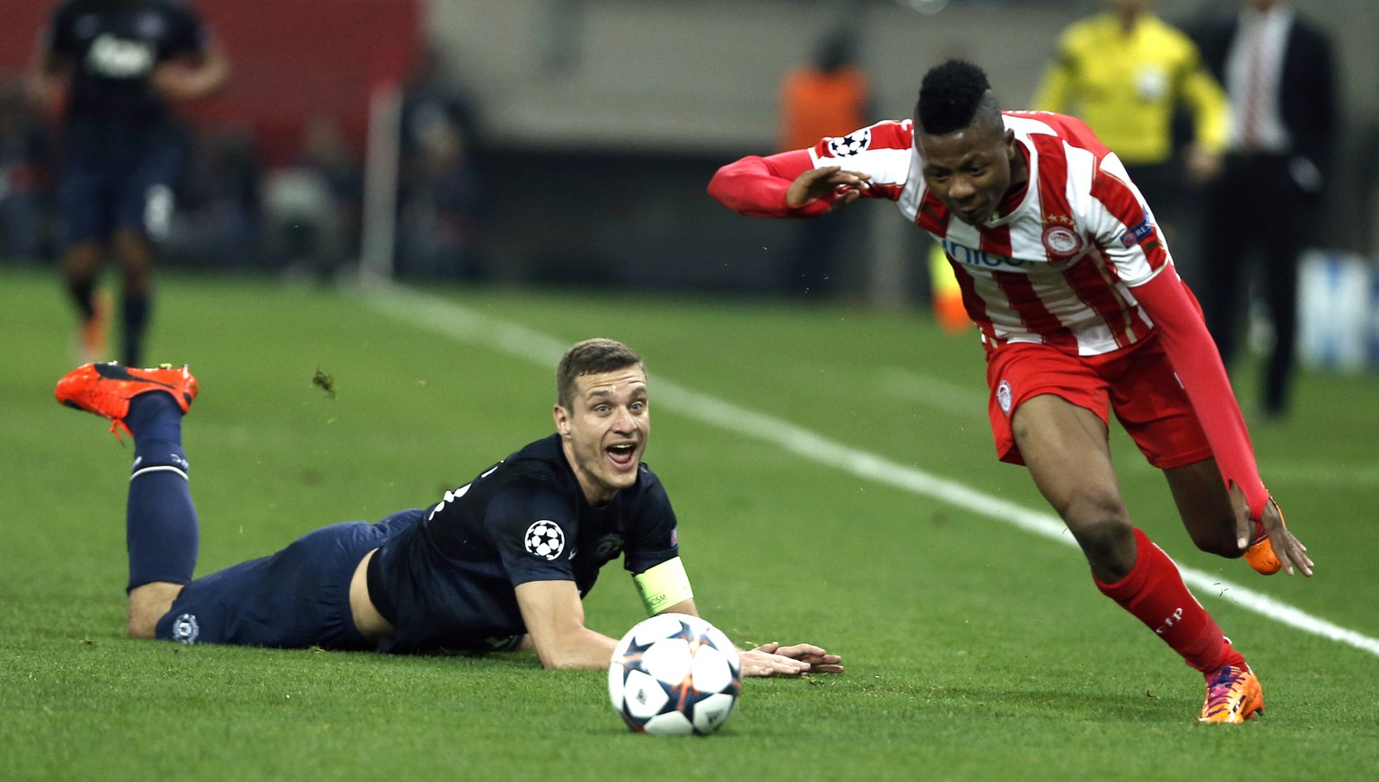 Olympiakos' Michael Olaitan right, goes for the ball as Manchester United's captain Nemanja Vidic looks on  during their Champions League, round of 16, first leg soccer match at Georgios Karaiskakis stadium, in Piraeus port, near Athens, on Tuesday, Feb. 25, 2014. (AP Photo/Petros Giannakouris)